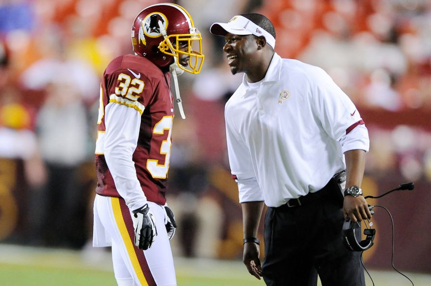 Raheem Morris (R) talks with Washington Redskins defensive back Brandyn Thompson (32) during a break in action. (Preston Keres/Special to The Washington Times)