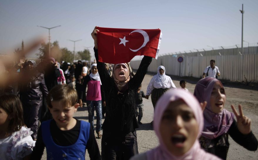 Syrians, who fled their homes due to fighting between the Syrian army and the rebels, shout slogans as they march toward the Turkish side of the border, during a protest asking the Turkish government to let them enter to their refugee camps, at the Bab Al-Salameh border crossing, near the Syrian town of Azaz, Tuesday, Aug. 28, 2012. (AP Photo/Muhammed Muheisen)
