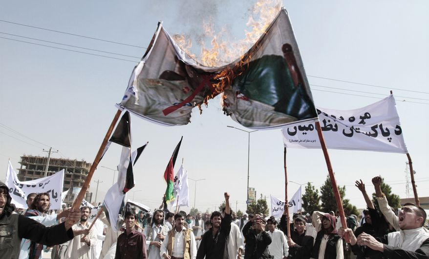 Afghan protesters burn a banner with the portrait of Pakistani President Asif Ali Zardari during an anti-Pakistan demonstration in Kabul, Afghanistan, on Thursday, Aug. 30, 2012. Hundreds demonstrated against mortar firing from Pakistan into Afghan territories. (AP Photo/Musadeq Sadeq)