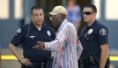 Preston Carter, 100, talks with police officers after police say his car went onto a sidewalk and plowed into a group of parents and children outside a South Los Angeles elementary school, Wednesday, Aug. 29, 2012. Nine children and two adults were injured in the wreck. (AP Photo/Mark J. Terrill)