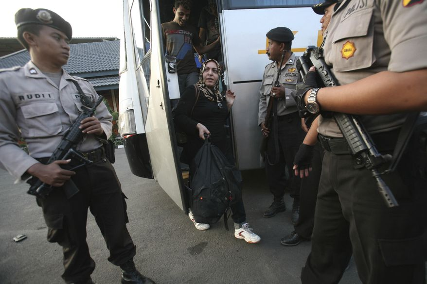 ** FILE ** Asylum seekers who were rescued from a troubled boat adrift in heavy seas off Java while trying to reach Australia are escorted by police officers upon their arrival at a marine police station in Surabaya, Indonesia, on Sunday, July 29, 2012. (AP Photo/Trisnadi)