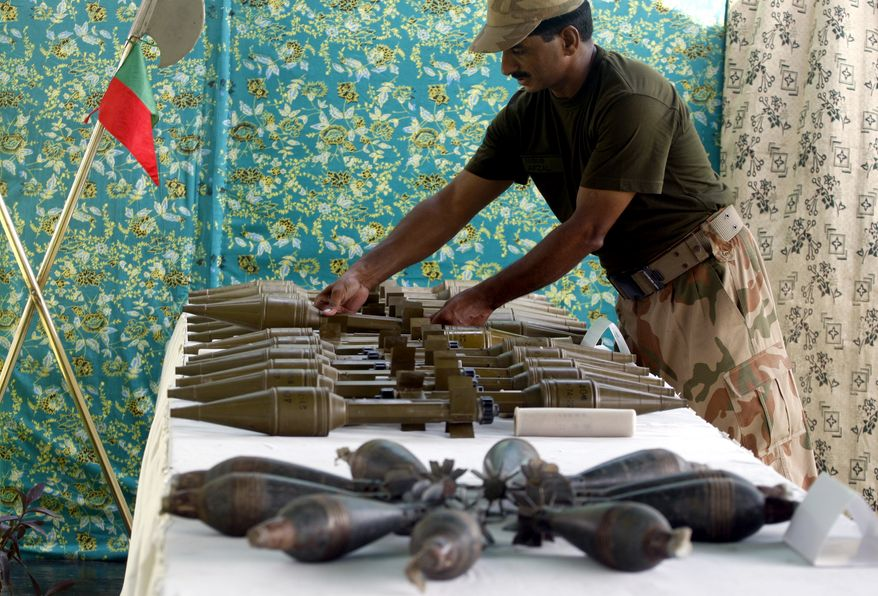 A Pakistani soldier arranges weapons reportedly recovered from hideouts of militants in tribal areas as the weapons are displayed in Peshawar, Pakistan, on Wednesday, Aug. 29, 2012. (AP Photo/Mohammad Sajjad)