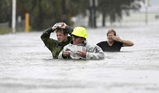 Chuck Cropp (center), his son, Piers (left), and wife, Liz, wade through floodwaters from Hurricane Isaac on Aug. 29, 2012, in New Orleans. (Associated Press)