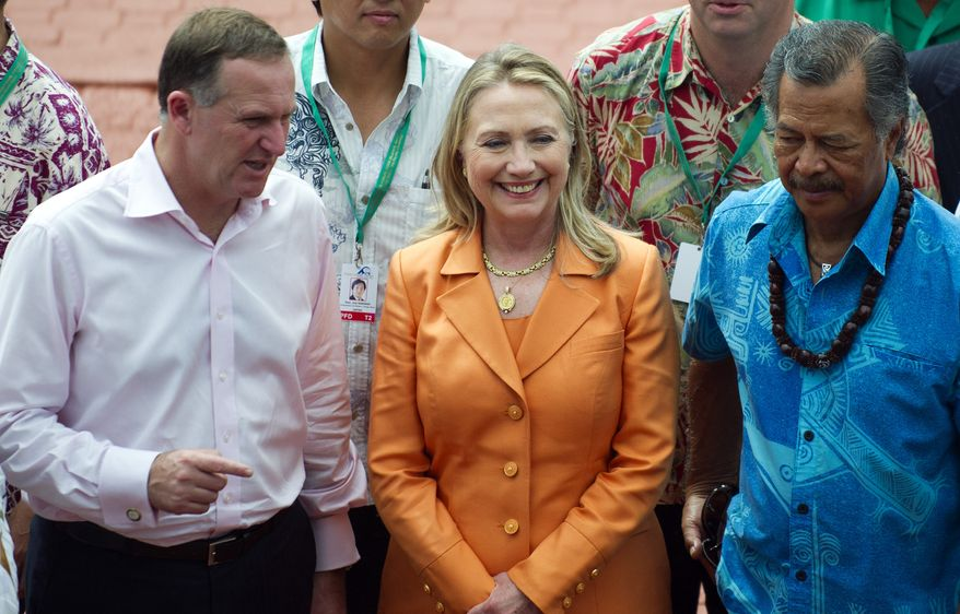 US Secretary of State Hillary Clinton, center, speaks with New Zealand Prime Minister John Key, left, and Cook Island Prime Minister Henry Puna, right, while posing for the family photo during the Pacific Island Forum Post-Forum Dialogue in Rarotonga, Cook Islands, Friday, Aug. 31, 2012. (AP Photo/Jim Watson, Pool)