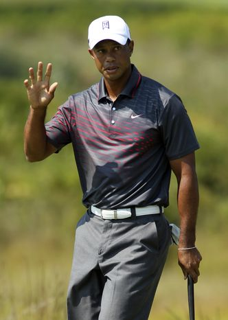 Tiger Woods waves to the crowd after make a birdie putt on the second hole during the first round of the Deutsche Bank Championship PGA golf tournament at TPC Boston in Norton, Mass., Friday, Aug. 31, 2012. (AP Photo/Stew Milne)