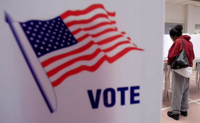 **FILE** A woman votes Jan. 31, 2012, at the Cuyahoga County Board of Elections in Cleveland as early voting began in Ohio's March 6 presidential primary. (Associated Press)