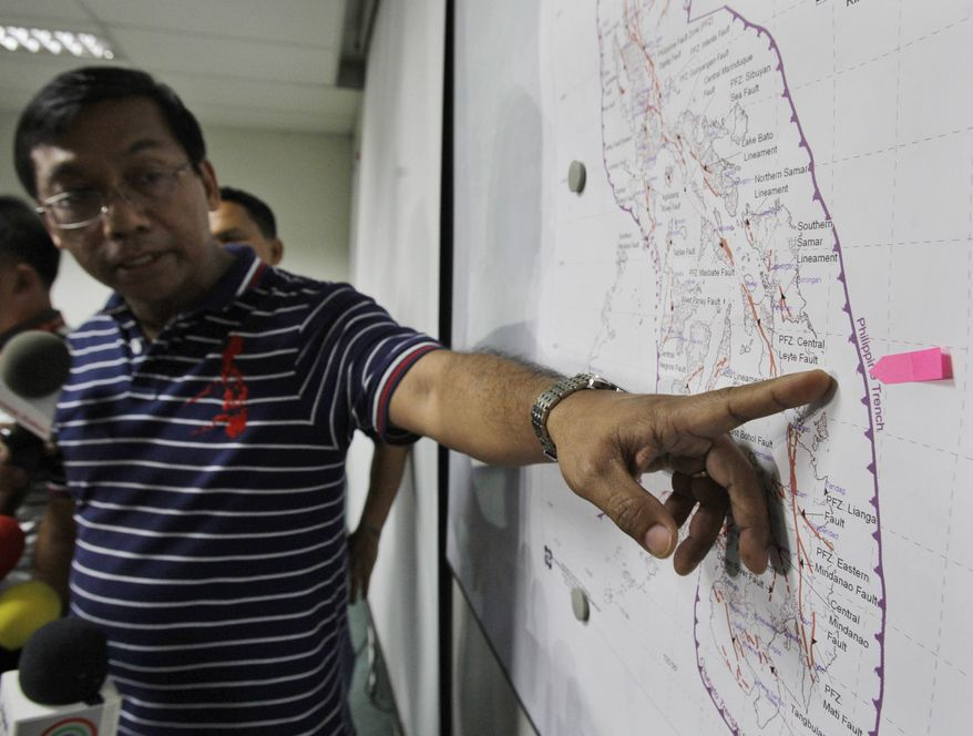 Renato Solidum, head of the Philippine seismology agency, points Aug. 31, 2012, during a press conference in suburban Quezon city, north of Manila, to an area on a Philippine map where the epicenter of a 7.6-magnitude earthquake happened that day. (Associated Press)