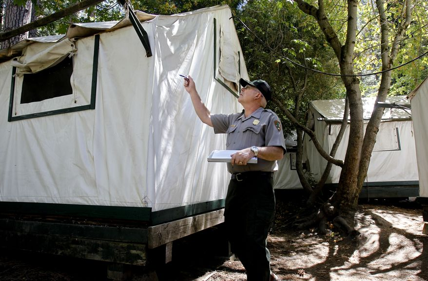 FILE - In a Tuesday Aug. 28, 2012 photo, Glenn Dean, a National Parks Occupational Safety and Health Specialist, inspects tent cabins for mice entry points at Curry Village at Yosemite National Park. Two more Yosemite National Park visitors have been found with a mouse-borne virus blamed for the deaths of two people, bringing the total number of infections to six, state health officials said. (AP Photo/San Francisco Chronicle, Michael Macor)