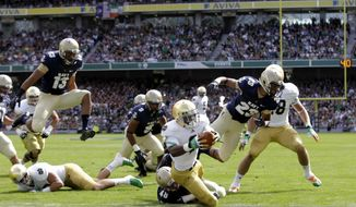 Notre Dame's Theo Riddick, centre, scores a touchdown, as he is tackled by Navy's Keegan Wezel during their NCAA college football game in Dublin, Ireland, Saturday, Sept. 1, 2012. (AP Photo/Peter Morrison)