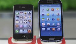 ** FILE ** Samsung Electronics' Galaxy S III, right, and Apple's iPhone 4S are displayed at a mobile phone shop in Seoul, South Korea, Friday, Aug. 24, 2012. (AP Photo/Ahn Young-joon)