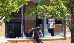 Police officers remove a computer hard drive from a Pathmark supermarket on Route 9 in Old Bridge, N.J., Friday, Aug. 31, 2012. Officials say a supermarket employee killed two people at the store early Friday and then fatally shot himself. (AP Photo/Rich Schultz)