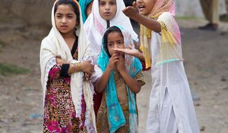 Pakistani Muslim girls talk about press gathered outside a mosque, unseen, where police arrested a Muslim cleric Khalid Chishti, in a suburb of Islamabad, Pakistan, Sunday, Sept. 2, 2012. In the latest twist in a religiously charged case that has focused attention on the country's harsh blasphemy laws, Pakistani police arrested Chishti who they say planted evidence in the case of a Christian girl accused of blasphemy. (AP Photo/Anjum Naveed)