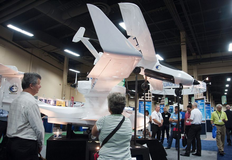 Attendees, of the Association for Unmanned Vehicle Systems International, North America 2012 conference checks out one of the exhibits displayed inside the exhibition hall of the Mandalay Bay hotel-casino in Las Vegas, Nev., on Wednesday, August 8, 2012. (Martin S. Fuentes/Special to The Washington Times)