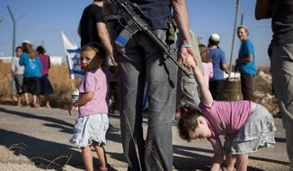 A Jewish settler stands with his daughters in the unauthorized West Bank settlement of Migron on Sunday, Aug. 26, 2012. (AP Photo/Sebastian Scheiner)