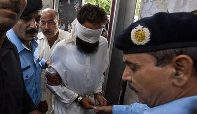 Pakistani police officers escort blindfolded Muslim cleric Khalid Chisti into court in Islamabad, Pakistan, on Sunday, Sept. 2, 2012. (AP Photo/Anjum Naveed)