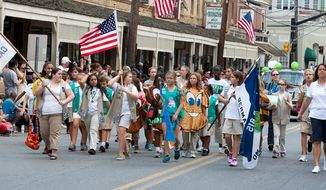 ** FILE ** Girl Scouts wave the flag while participating in the Labor Day parade in Gaithersburg, Md., in 2012. (The Washington Times)