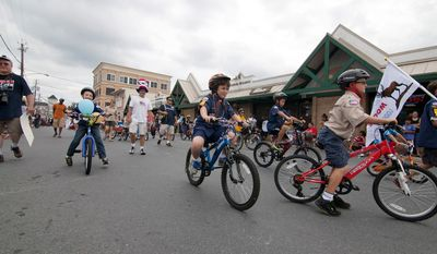 Boy Scout Pack 210 ride their bikes in the Gaithersburg end-of-summer parade.  (Craig Bisacre/The Washington Times)