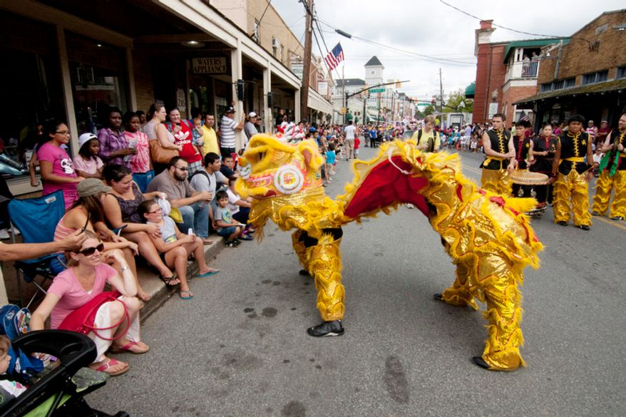 A giant dragon was one of 80 groups participating in the three hour long parade in Gaithersburg.  (Craig Bisacre/The Washington Times)