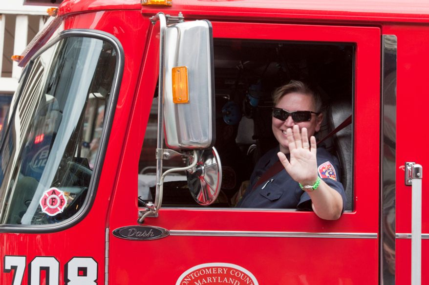 A firefighter waves from a firetruck during the Labor Day parade in Gaithersburg, Maryland.  (Craig Bisacre/The Washington Times)