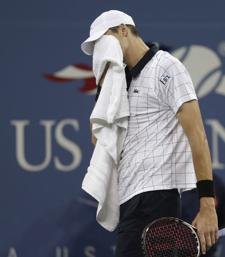 John Isner wipes his face after losing a point go Philipp Kohlschreiber, of Germany, in the third round of play at the 2012 US Open tennis tournament, early Monday, Sept. 3, 2012 in New York. The match began on Sunday evening. (AP Photo/Charles Krupa)