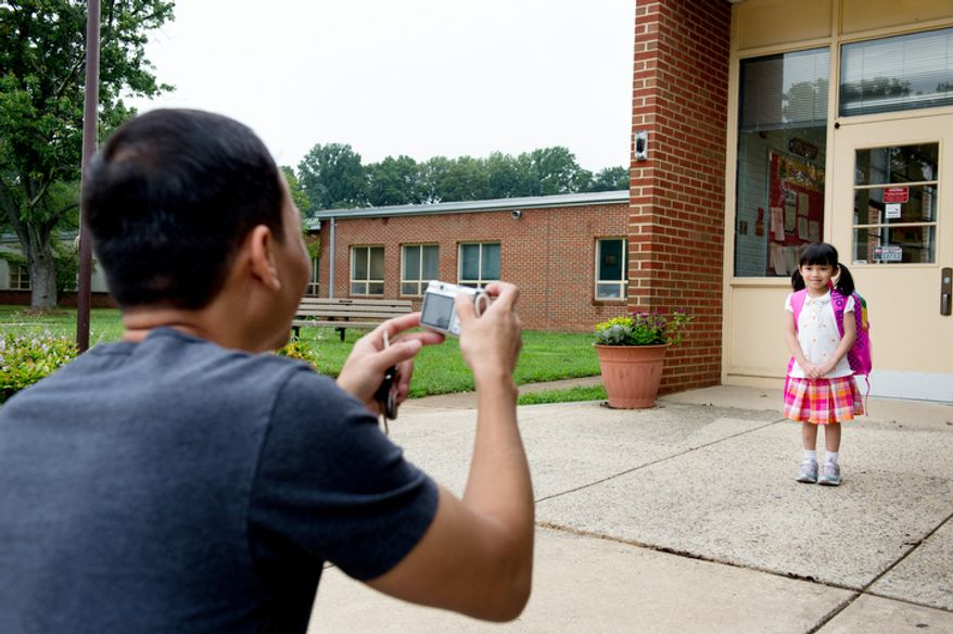 Stephan Mai, left, photographs Sarah, 5, on her first day of kindergarden at North Springfield Elementary School. (Andrew Harnik/The Washington Times)