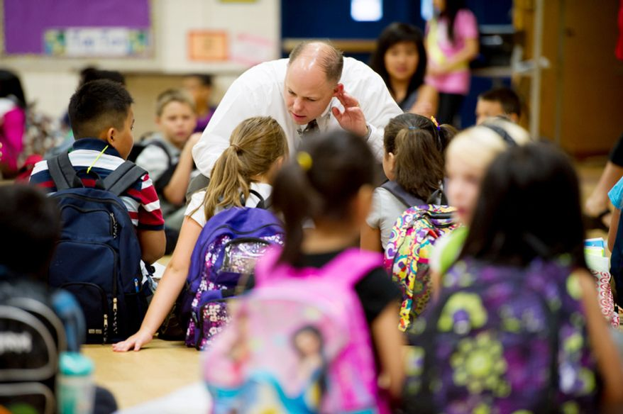 Principal Chad McRae talks with students before they head to class on the first day back to school. (Andrew Harnik/The Washington Times)