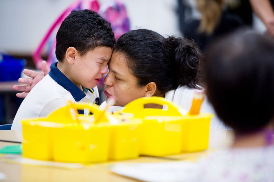 Sandra Mejia comforts her son Carlos Jiron, 5, on his first day of kindergarden. (Andrew Harnik/The Washington Times)
