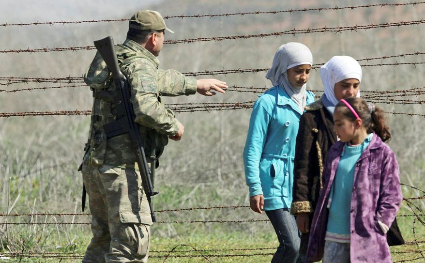 A Turkish soldier helps young Syrian refugees clear the barbed wire fence at a border crossing near Reyhanli, Turkey, earlier this year. The number of Syrian refugees living in border camps in Turkey is now estimated at 80,000, and Turkey says that is close to its maximum capability for providing them shelter. (Associated Press)