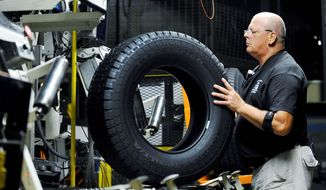 Tire inspector Buddy Rice checks for defects in the tire-verification area at a Michelin manufacturing plant in Greenville, S.C., in July. U.S. factory activity shrank for the third straight month in August as new orders, production and employment all fell. Weak consumer spending and steady declines in business orders for large machinery are slowing factory output. (Associated Press)