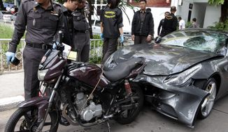 Thai police officers inspect a motorcycle and a Ferrari involved in a hit-and-run accident during an investigation at Thong Lor police station in Bangkok on Monday. A grandson of the creator of the Red Bull energy drink has been arrested for driving the Ferrari that struck a police officer and dragged his dead body down a Bangkok street in a hit-and-run. (Associated Press)