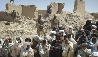 In this Saturday, Aug. 27, 2011, photo, Afghan men listen to speeches, as Afghan and U.S. soldiers stand guard, background, in Washer district, Helmand province, south of Kabul, Afghanistan. (AP Photo/Abdul Khaleq)