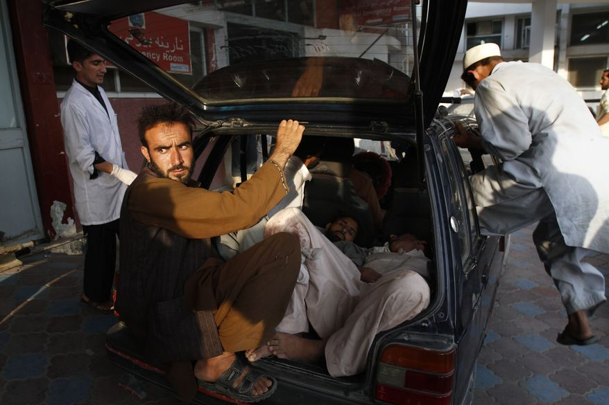 Injured Afghan men arrive by car at a hospital after a suicide attack on a funeral in the Durbaba district of Jalalabad, east of Kabul, Afghanistan, on Tuesday, Sept. 4, 2012. (AP Photo/Rahmat Gul)