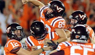 Virginia Tech kicker Cody Journell (89) celebrates with Trey Gresh (12) and George George (48) after making a 17-yard field goal in overtime to win a college football game against Georgia Tech, Monday, Sept. 3, 2012, in Blacksburg, Va. Virginia Tech won 20-17. (AP Photo/Don Petersen)
