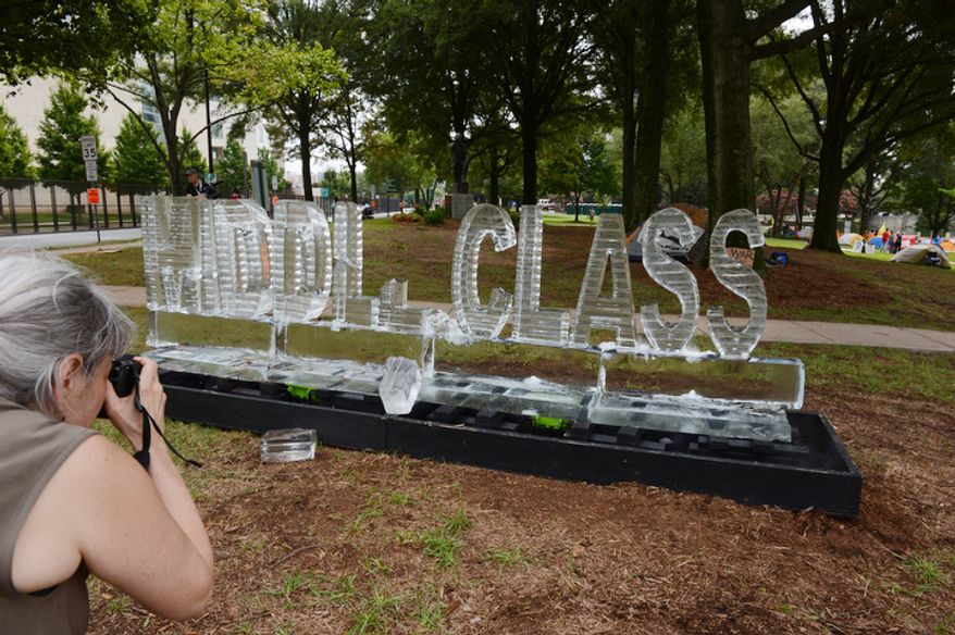 "A woman takes a picture of an ice sculpture that says ""Middle Class"" on Tuesday, Sept. 3, 2012 in Marshall Park in Charlotte, N.C., which has been taken over by the Occupy movement during the Democratic National Convention. The sculpture, which was made by artists Ligorano and Reese, is called ""Morning in America"" and is supposed to represent the fact that the middle class is disappearing like ice. (Barbara L. Salisbury/The Washington Times)"