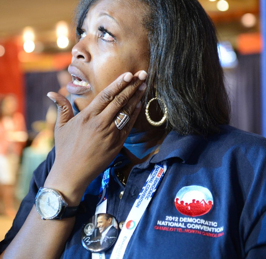 Convention volunteer Regina Davidson wipes away a tear while watching a speech at the Democratic National Convention. (Barbara Salisbury/ The Washington Times)