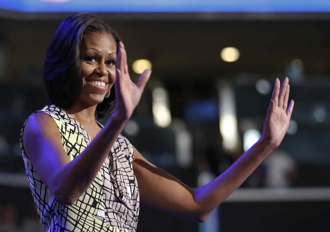 First lady Michelle Obama waves as she appears at the podium for a camera test on the stage at the Democratic National Convention inside Time Warner Cable Arena in Charlotte, N.C., on Monday, Sept. 3, 2012. (AP Photo/Jae C. Hong)