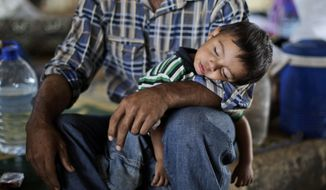 Ghassan Khalil, 30, who fled his home in Marea, Syria, 12 days before because of government shelling of his house, holds his sleeping son Mahmoud, 2, who suffers with a fever, as they take refuge at the Bab Al-Salameh border crossing near Azaz, Syria, on Monday, Sept. 3, 2012, in hopes of entering a refugee camp in Turkey. (AP Photo/Muhammed Muheisen)