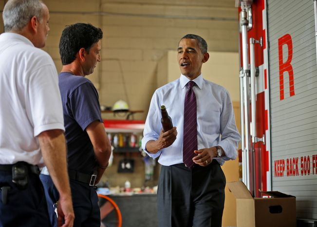 President Obama holds up a bottle of beer Sept. 4, 2012, as he delivers a case of White House brewed beer to the firefighters at Fire Station No. 14 in Norfolk, Va., during an unscheduled campaign stop. (Associated Press)