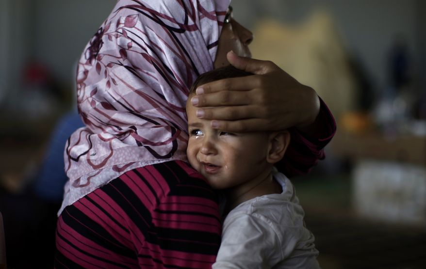 Amjad Al-Saleh, a Syrian child suffering from food poisoning, is comforted by his mother as they take refuge at the Bab Al-Salameh border crossing near Azaz, Syria, on Wednesday, Sept. 5, 2012, in hopes of entering a refugee camp in Turkey. The Al-Saleh family left their home in Marea, Syria, 11 days before when government forces shelled their house. (AP Photo/Muhammed Muheisen)