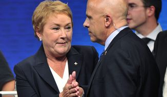 Parti Quebecois leader Pauline Marois speaks with a member of her security detail after being whisked off the stage by Surete du Quebec police officers as she delivered her victory speech in Montreal on Tuesday, Sept. 4, 2012. (AP Photo/Paul Chiasson, Canadian Press)