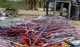 Fireworks lie in the foreground and policemen arrive at the scene after a massive blaze swept through the Om Siva Shakti fireworks factory in Sivakasi, about 650 kilometers (400 miles) southwest of Chennai, India, Wednesday, Sept. 5, 2012. Dozens of workers were killed and dozens were injured in the fire, the cause of which was not immediately known. (AP Photo)