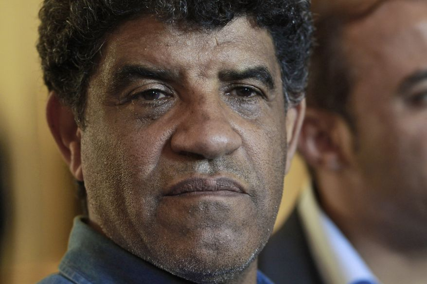 ** FILE ** Abdullah Senussi, head of Libyan intelligence, speaks to the press during a government-sponsored media tour as gunfire erupts all around the Rixos hotel in Tripoli, Libya, on Sunday, Aug. 21, 2011. (AP Photo/Dario Lopez-Mills)