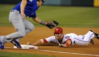 Washington Nationals' Bryce Harper steals third base on a wild pitch as Chicago Cubs third baseman Josh Vitters, left, applies a late tag during the seventh inning of their baseball game, Tuesday, Sept. 4, 2012, in Washington. Harper scored on teammate Jayson Werth's single to right field. (AP Photo/Richard Lipski)