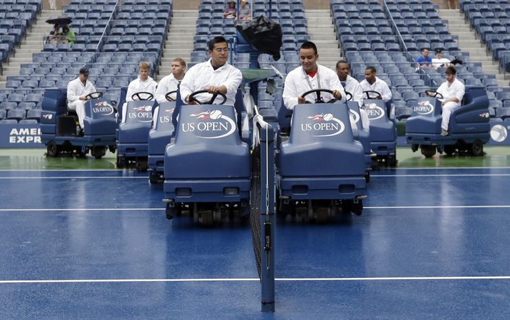 "Workmen drive ""Slamboni"" machines to dry the court at Arthur Ashe Stadium during a rain delay at the 2012 US Open tennis tournament,  Wednesday, Sept. 5, 2012, in New York. (AP Photo/Darron Cummings)"