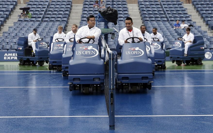 """Workmen drive """"Slamboni"""" machines to dry the court at Arthur Ashe Stadium during a rain delay at the 2012 US Open tennis tournament,  Wednesday, Sept. 5, 2012, in New York. (AP Photo/Darron Cummings)"""