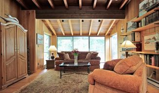 The living room has a wall of glass doors and a wood-beamed cathedral ceiling. It also features a stone fireplace.