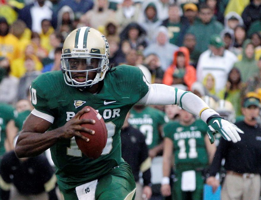 FILE - This Dec. 3, 2011 file photo shows Baylor quarterback Robert Griffin III (10) finding running room behind the line of scrimmage against Texas in the first half of an NCAA college football game in Waco, Texas. Griffin III has won The Associated Press college football player of the year, adding another award to his impressive postseason haul. (AP Photo/Tony Gutierrez, File)