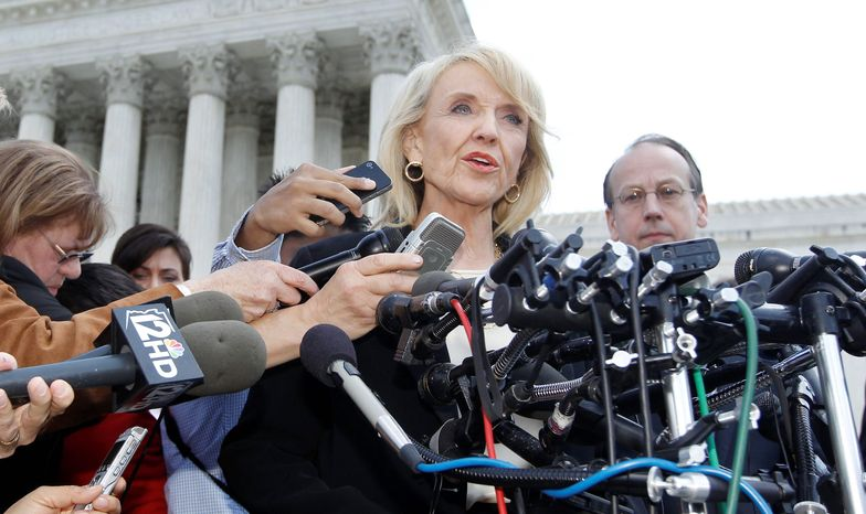 Gov. Jan Brewer two years ago signed landmark legislation requiring all Arizona police officers to check the immigration status of people they stop while enforcing other laws and suspect are in the country illegally. The requirement is expected to go into effect in the next several days. (Associated Press)