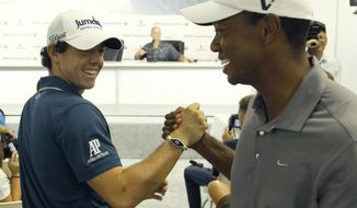 Rory McIlroy of Northern Ireland, left, shakes with Tiger Woods between interviews during the Pro-Am of the BMW Championship PGA golf tournament at Crooked Stick Golf Club in Carmel, Ind., Wednesday, Sept. 5, 2012. (AP Photo/Charles Rex Arbogast)