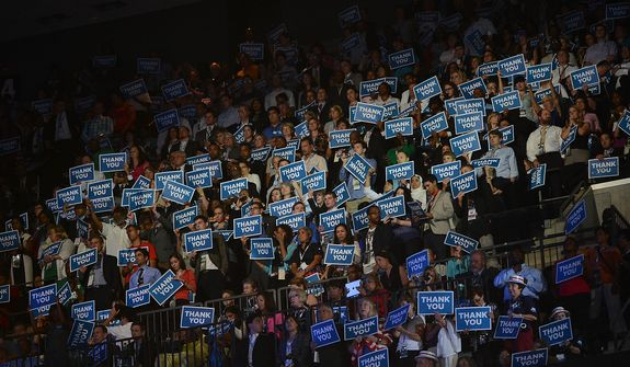 Democrats hold up Thank You signs as Admiral John B. Nathman United States Navy, Retired, honors America's military veterans and promotes President Barack Obama policies for veterans at the Democratic National Convention in the Time Warner Cable Arena in Charlotte, N.C., on Thursday, September 6, 2012.  (Andrew Geraci/ The Washington Times)